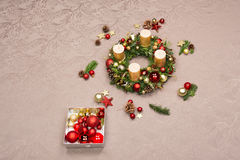 用红色和金子圣诞节装饰装饰的新鲜的手工制造圣诞节花圈,冷杉锥体和核桃与金蜡烛 免版税库存图片