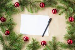 用红色圣诞节球装饰的杉树分支作为在一个土气假日背景框架的边界与拷贝空间笔 免版税库存图片