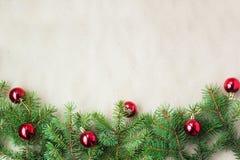 用红色圣诞节球装饰的杉树分支作为在一个土气假日背景框架的边界与拷贝空间 库存图片