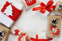 用红色弓装饰的圣诞节礼物礼物在白色木背景的一个圈子被安排 平的位置,顶视图 免版税库存图片