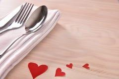 用红色心脏装饰的表为情人节举起了木头 图库摄影