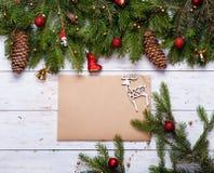 用红色球、诗歌选和绿色云杉的分支装饰的圣诞卡 库存图片
