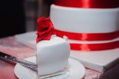 用红色花、玫瑰、丝带和弓装饰的华美的白蛋糕 免版税库存照片