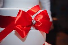 用红色花、玫瑰、丝带和弓装饰的华美的白蛋糕 图库摄影