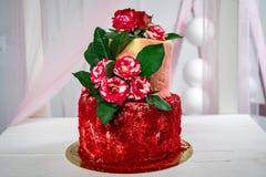 用红色花装饰的一个可口两层手工制造蛋糕 水平的框架 免版税库存图片