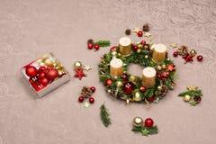 用红色装饰的新鲜的手工制造圣诞节花圈和金子圣诞节装饰、冷杉锥体和核桃与蜡烛 免版税库存照片