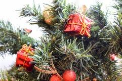 用红色,小礼物、玩具、金黄叶子和球装饰的一棵绿色新年树的分支 库存图片