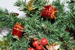 用红色,小礼物、玩具、金黄叶子和球装饰的一棵绿色新年树的分支 免版税库存照片