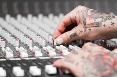 用纹身花刺报道的手特写镜头运作在搅拌器控制台,扭转瘤,演播室设备概念 库存照片