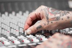 用纹身花刺报道的手特写镜头运作在搅拌器控制台,扭转瘤,演播室设备概念 免版税库存照片