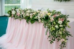 用绿叶和长的布料装饰的新婚佳偶的美丽的白色饭桌 八仙花属,玫瑰,g长的插花  库存图片