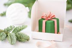 用绿色丝绒盖的微型奶油甜点酥皮点心点心 个别地包裹在白色箱子 云杉分支在bokeh的 库存图片