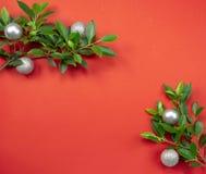 用绿色叶子和g装饰的红色圣诞节纸背景 库存照片