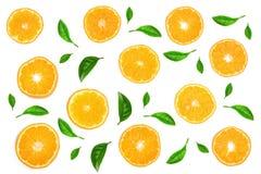 用绿色叶子或蜜桔装饰的切片桔子隔绝在白色背景,顶视图 果子构成 免版税库存图片