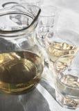 用美丽的阴影和玻璃充满的自创白色希腊酒,在桌在一个小酒馆在阳光下和蒸馏瓶 免版税库存照片