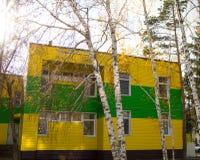 用美丽的黄色和绿色房屋板壁盖的两层大厦 库存图片