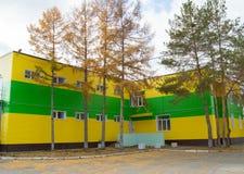 用美丽的黄色和绿色房屋板壁盖的两层大厦 免版税库存图片
