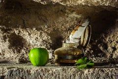用羽毛装饰在古色古香的墨水壶和一个苹果在砂岩洞背景中 库存照片