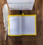 用羽毛装饰笔,在木桌上的noteand后面墨水壶 免版税库存照片