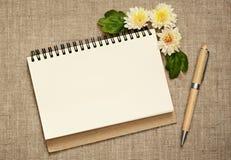 用翠菊和笔装饰的笔记薄 库存照片