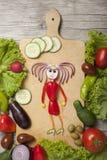 用胡椒和葱藏品厨房工具做的女孩 免版税库存照片