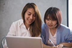 用膝上型计算机和咖啡的亚裔妇女 工作在咖啡店的自由职业者 工作在办公室生活方式之外 免版税库存图片