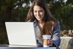 用膝上型计算机饮用的咖啡的少妇女孩 免版税库存图片