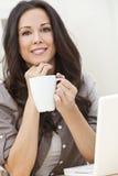 用膝上型计算机饮用的茶或咖啡的妇女 图库摄影