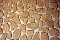 用自然石头和不规则形状片断盖的墙壁  免版税库存图片