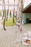 用花和丝带装饰的一部分的婚礼曲拱在有心脏的木板箱附近 库存图片
