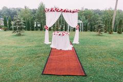 用花和垂悬的豆和桌的装饰的水平的看法婚礼曲拱安置在草甸 免版税库存图片