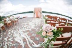 用花和木椅子装饰的婚礼曲拱在森林湖背景 库存照片