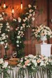用花和植物装饰的婚礼桌服务的宴会,在木背景的减速火箭的灯 库存图片