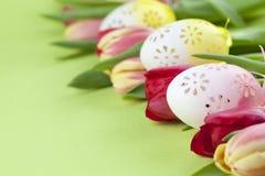 用花装饰的复活节彩蛋和郁金香边界 免版税库存图片
