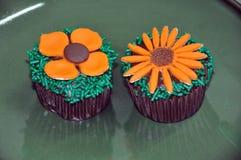 用花装饰的巧克力杯形蛋糕 免版税库存照片