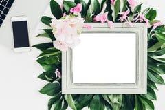 用花装饰的木制框架和叶子、膝上型计算机和电话 文本的空的空间 免版税库存图片