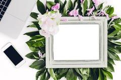 用花装饰的木制框架和叶子、膝上型计算机和电话 文本的空的空间 库存图片