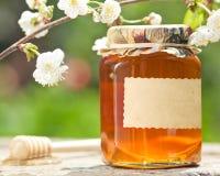 用花装饰的玻璃蜂蜜瓶子 图库摄影