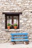 用花装饰的窗口和蓝色长凳 库存图片