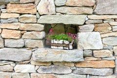 用花装饰的老石墙 库存图片