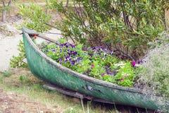 用花装饰的被放弃的小船 库存照片