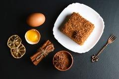 用茴香星层状蜜糕Medovik装饰的切片,点心叉子,烘干了柠檬,桂香棍子,未加工的鸡蛋,可可粉战俘 图库摄影