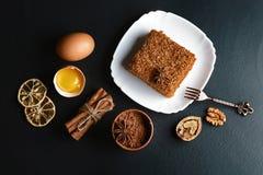 用茴香星装饰的切片层状蜜糕,点心叉子,烘干了柠檬,桂香棍子,未加工的鸡蛋,可可粉,坚果, clos 免版税库存图片