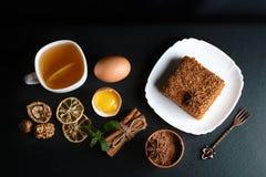 用茴香星装饰的切片层状蜜糕,点心叉子,薄菏,烘干了柠檬,桂香棍子,未加工的鸡蛋,可可粉,坚果 免版税库存照片