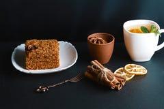 用茴香星装饰的切片层状蜜糕,点心叉子,薄菏,烘干了柠檬,桂香棍子,未加工的鸡蛋,可可粉,杯子 图库摄影