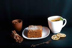 用茴香星装饰的切片层状蜜糕,点心叉子,薄菏,烘干了柠檬,桂香,可可粉,茶棍子机智 免版税库存图片