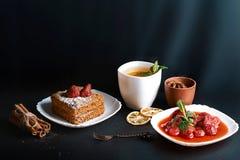 用茴香星装饰的切片层状蜜糕,点心叉子,薄菏,烘干了柠檬,桂香,草莓酱,可可粉棍子  免版税库存照片
