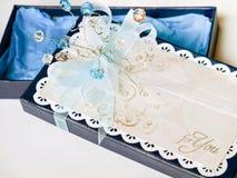 用蓝色和白色宝石、白色鞋带和被盖印的纸装饰的手工制造礼物盒 库存照片