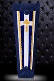 用蓝色和白色布料盖的闭合的棺材装饰用教会在灰色背景的金十字架 垂直位置 免版税库存照片