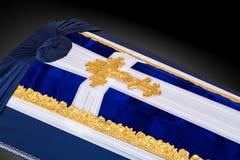用蓝色和白色布料盖的闭合的棺材装饰用教会在灰色豪华背景的金十字架 特写镜头 库存照片